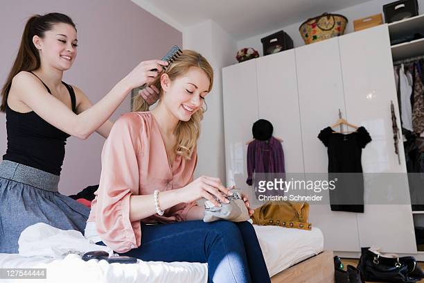 Teenage girl combing friends hair