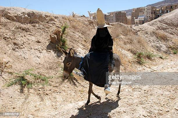 Teenage girl completely covered in black Muslim garb and tall straw hat riding donkey.