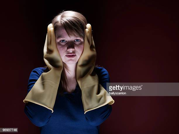 Teenage Girl Covering Ears With Rubber Gloves.