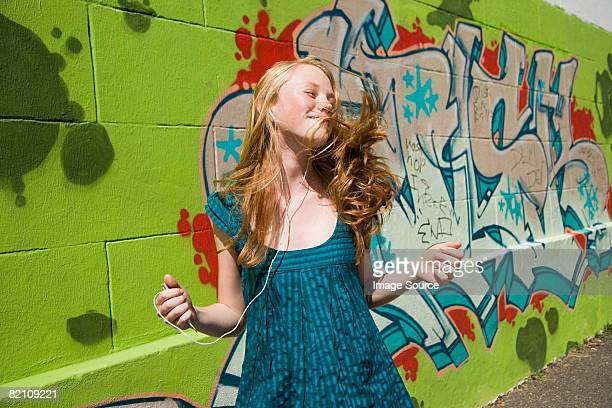A teenage girl dancing and listening to music