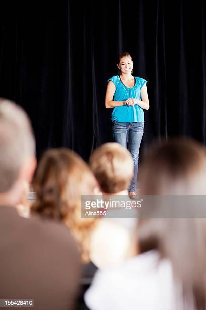 10 代の少女がステージにスピーチをお届けするために、対象者