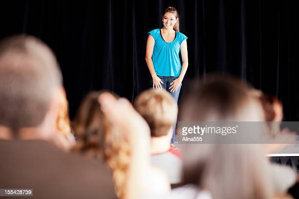 Teenage girl delivering a speech on stage for an audience