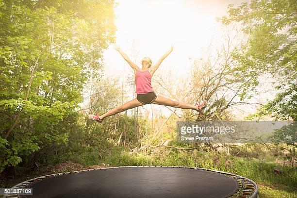 Teenage girl doing star jump on trampoline, outdoors