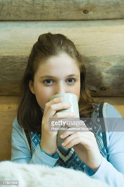 Teenage girl drinking hot beverage, looking at camera
