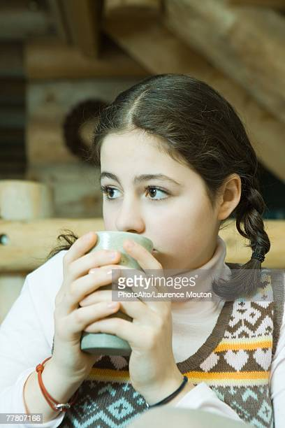 Teenage girl drinking hot beverage, looking away