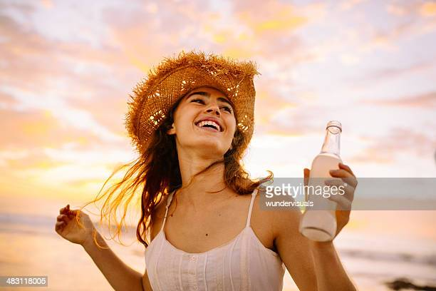 Teenage girl drinking lemonade in sunset