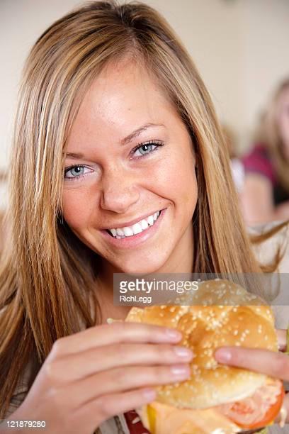 Jeune fille mangeant un Cheeseburger