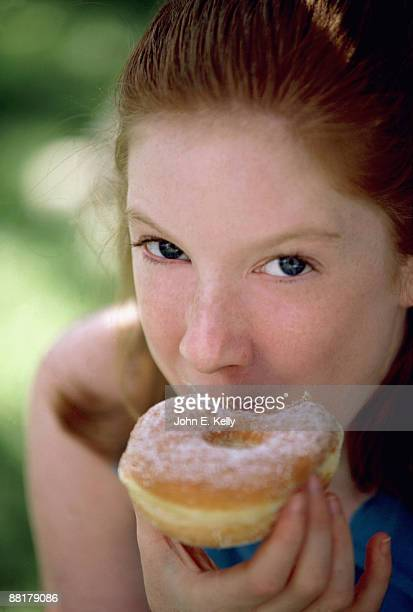 Teenage girl eating a donut