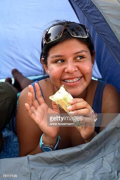 Teenage girl (15-17) eating candybar in tent