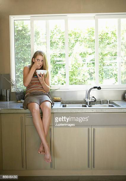 Teenage girl eating cereal in kitchen
