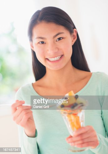 Teenage girl eating fruit dessert : Stock Photo