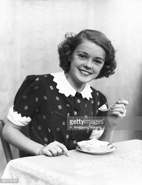 Teenage girl eating ice-cream, portrait.