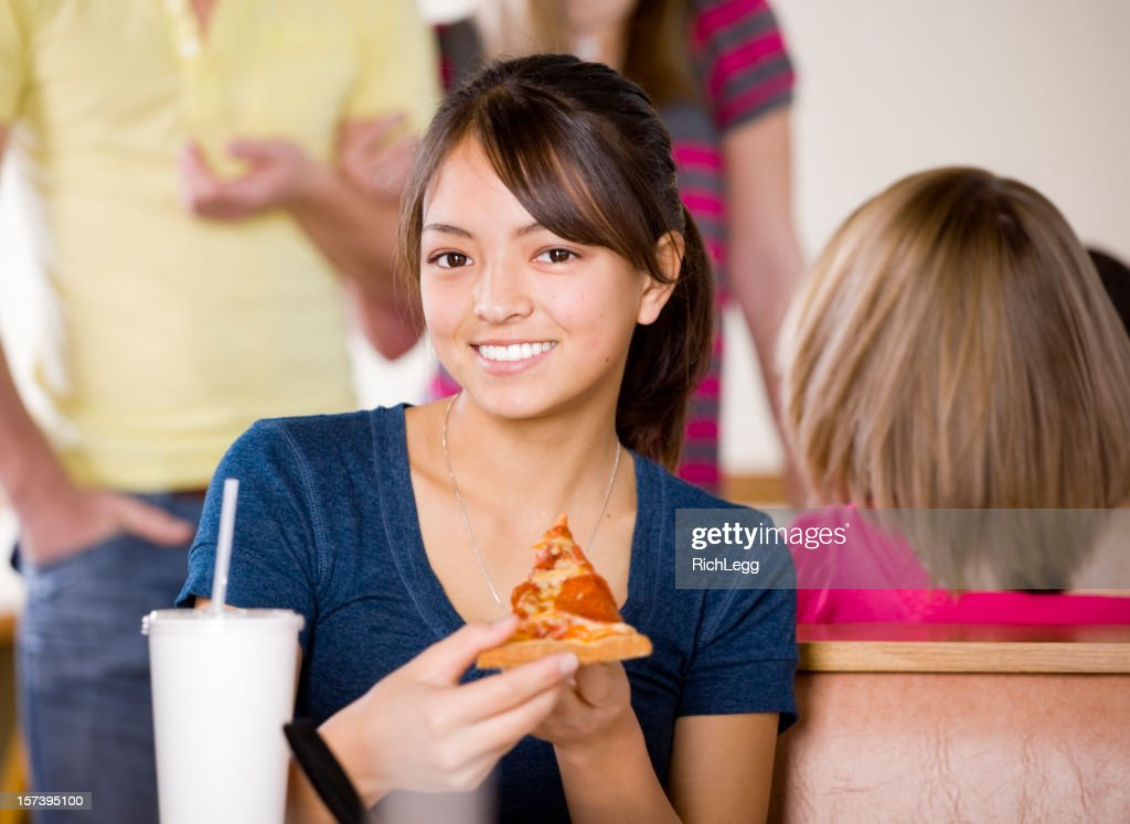 Teenage Girl Eating Pizza In Fast Food Restaurant : Stock Photo