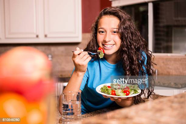 Teenage girl eating salad for dinner after school.