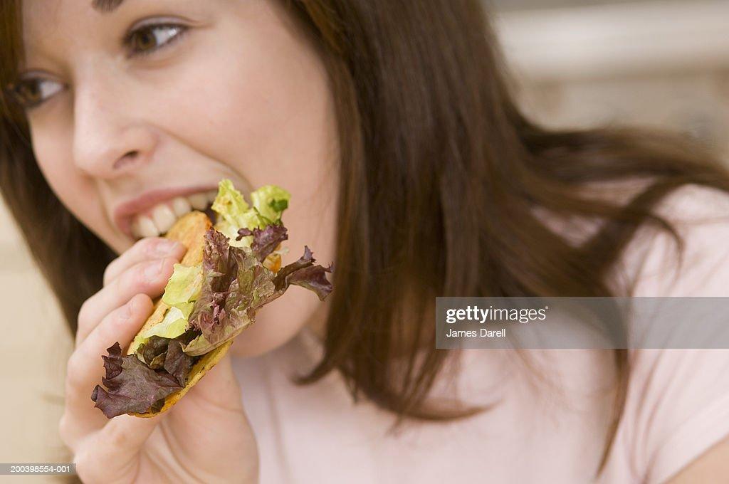 Teenage girl (15-17) eating tacho, close-up