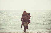 A man is giving his girlfriend a piggyback ride in the shallow water.