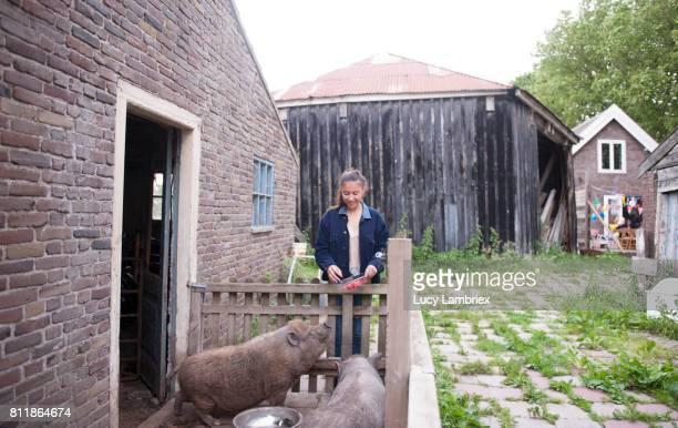 Teenage girl feeding raspberries to the pigs