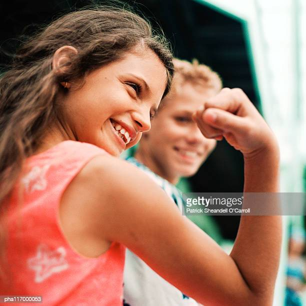 Teenage girl flexing arm muscles, smiling