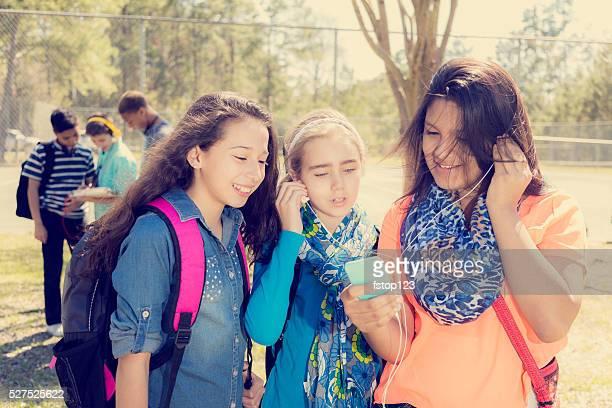 Teenage girl friends listen to music on smart phone.  Park.