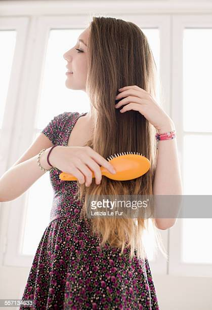 Teenage girl getting hair care with brush