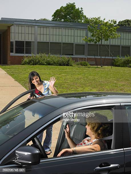 Teenage girl (13-15) getting out of mother's car in front of school