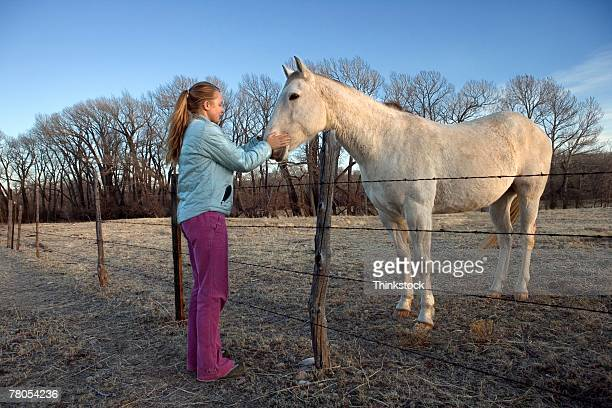 Teenage girl greeting horse