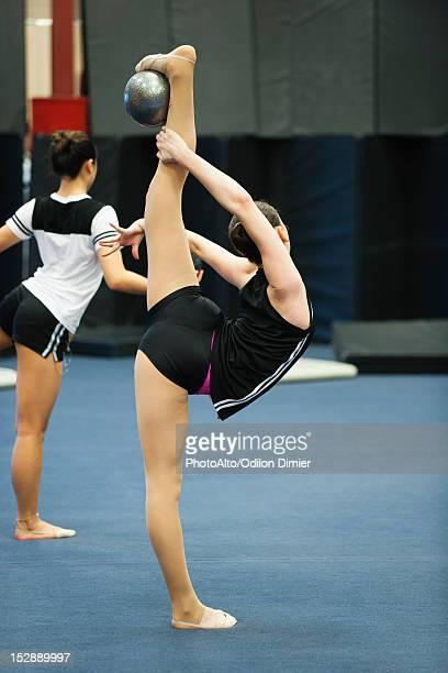 Teenage girl gymnasts practicing rhythmic gymnastics