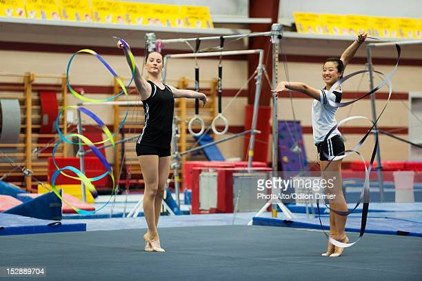 Teenage girl gymnasts practicing rhythmic gymnastics, twirling ribbons