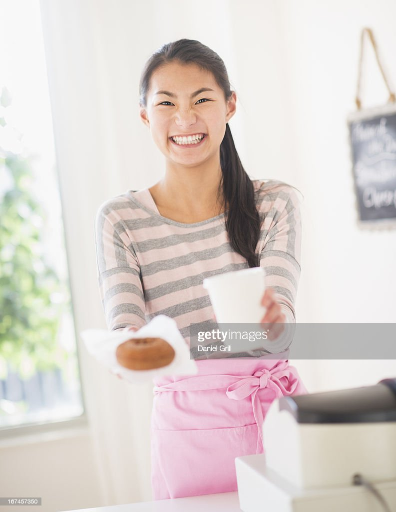 Teenage girl handing order : Stock Photo