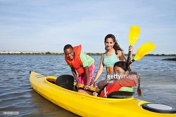 Teenage girl helping children with kayak
