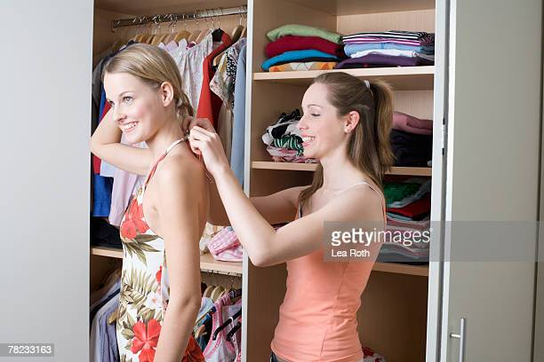teenage girl helping her friend getting dressed in front of open wardrobe