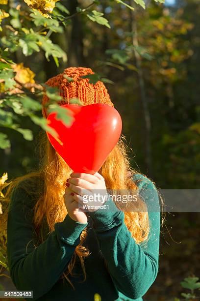 Teenage girl hiding her face behind heart shaped balloon