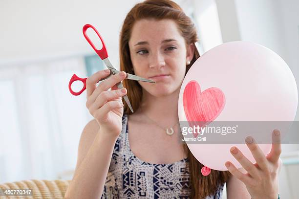 Teenage girl (14-15) holding balloon and scissors