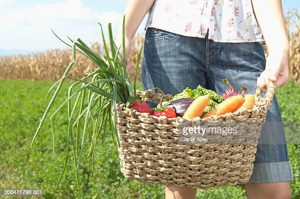 Teenage girl (16-18) holding basket of vegetables, mid section