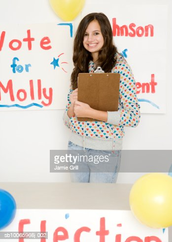 Teenage girl (14-15) holding clipboard running for president election, smiling, portrait : Stock Photo