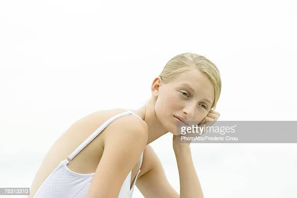 Teenage girl holding head, looking away