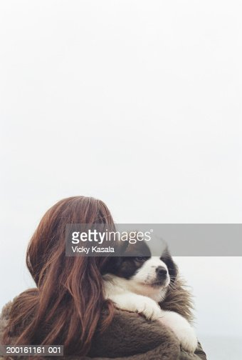 Teenage girl (15-17) holding puppy over shoulder, rear view