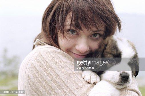 Teenage girl (15-17) holding Saint Bernard puppy, portrait