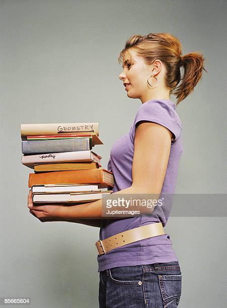 Teenage girl holding stack of books