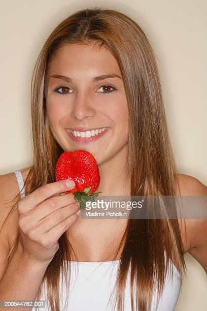 Teenage girl (13-15) holding strawberry, smiling, close-up, portrait