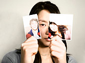 Teenage girl (15-17) holding up torn photograph, portrait, close-up