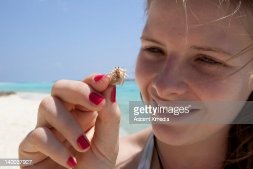 Teenage girl holds hermit crab, white beach behind : Stock Photo