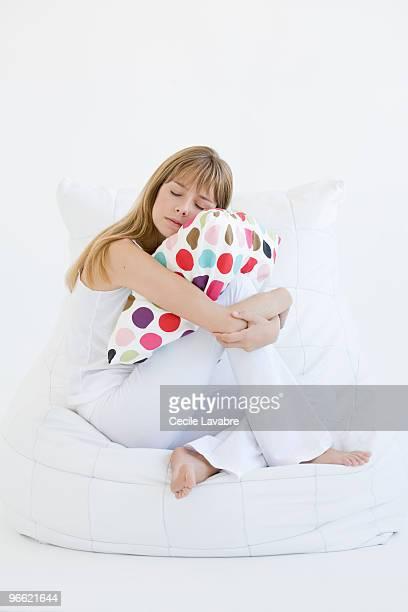 Teenage girl hugging a pillow