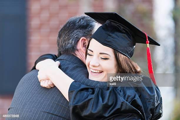 Menina adolescente agarrar Pai vestindo Traje Académico