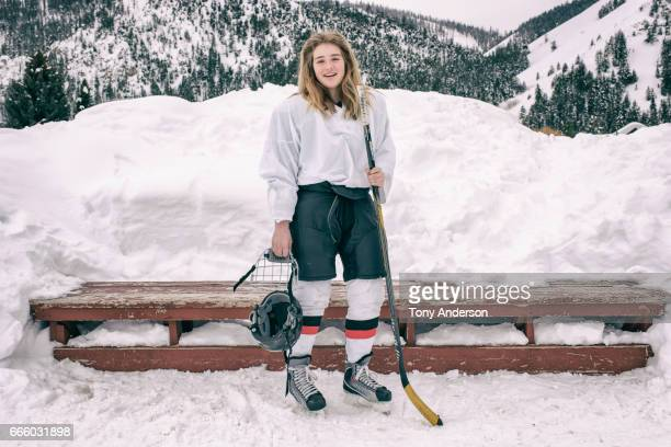 Teenage girl ice hockey player standing near bench outdoors in winter