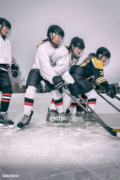 Teenage girl ice hockey players clashing on outdoor rink in winter