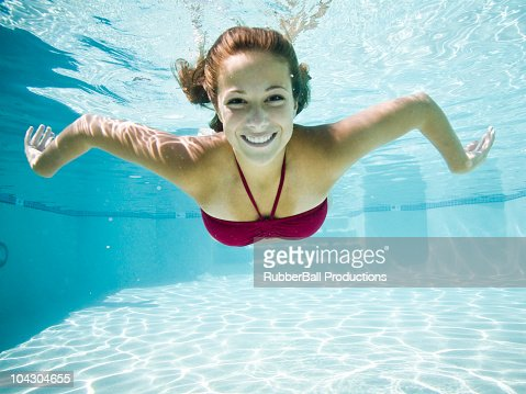 teenage girl in a bathing suit swimming in a pool : Stock Photo