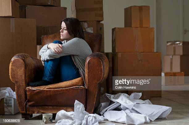 Teenage girl in armchair in new home