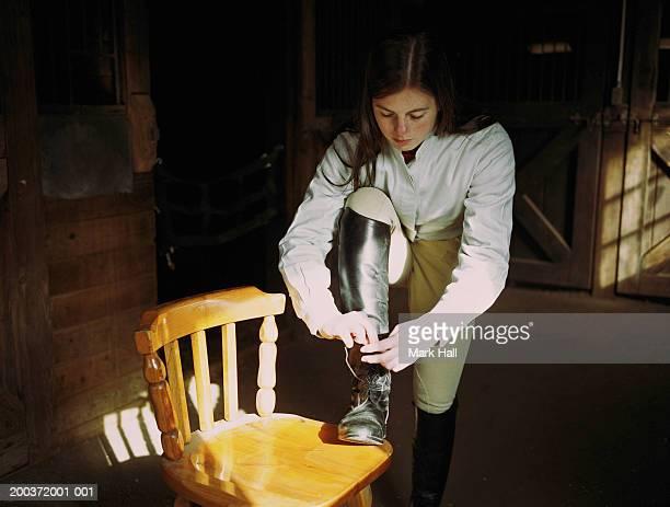 Teenage girl (17-19) in barn, tying boot