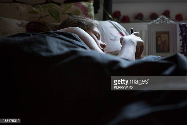 Teenage girl in bed on her phone